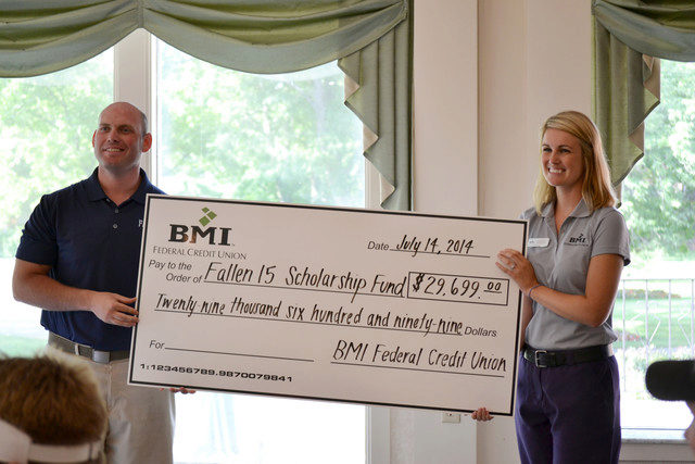 BMI director presenting large check to Fallen 15 director