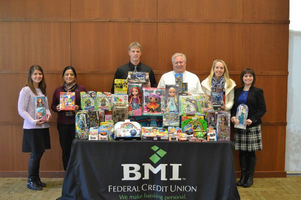 bmi fcu employees posing with a table of donated toys for children
