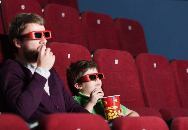boy and father in 3D glasses at movies