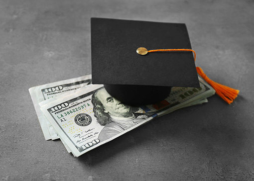 diploma and graduation hat with rolled up money