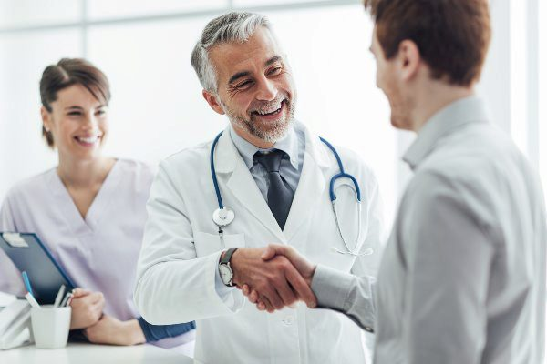 doctor and nurse shaking patients hand smiling