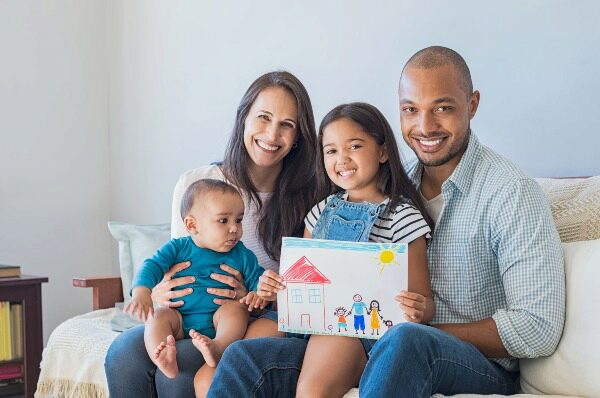 family with daughter holding drawing of house
