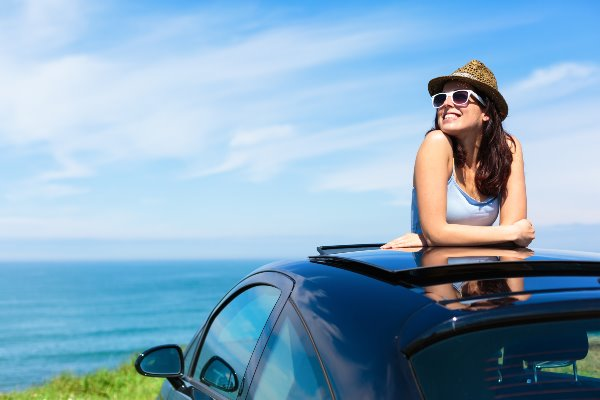 girl in parked car with sunroof open